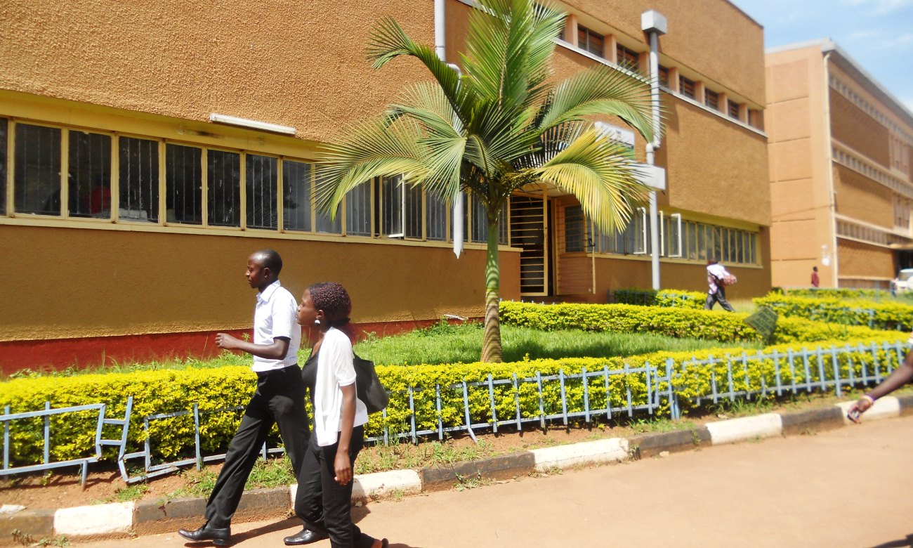 A male and female student walk past the E-Learning and Teacher Education Building, College of Education and External Studies, Makerere University, Kampala Uganda.