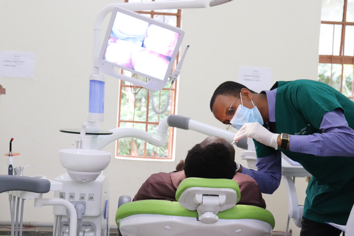 A Bachelor of Dental Surgery (BDS) student conducts a free dental checkup on a client during the Dental Hospital and School Opening Week on 20th August 2019, Makerere University, Kampala Uganda