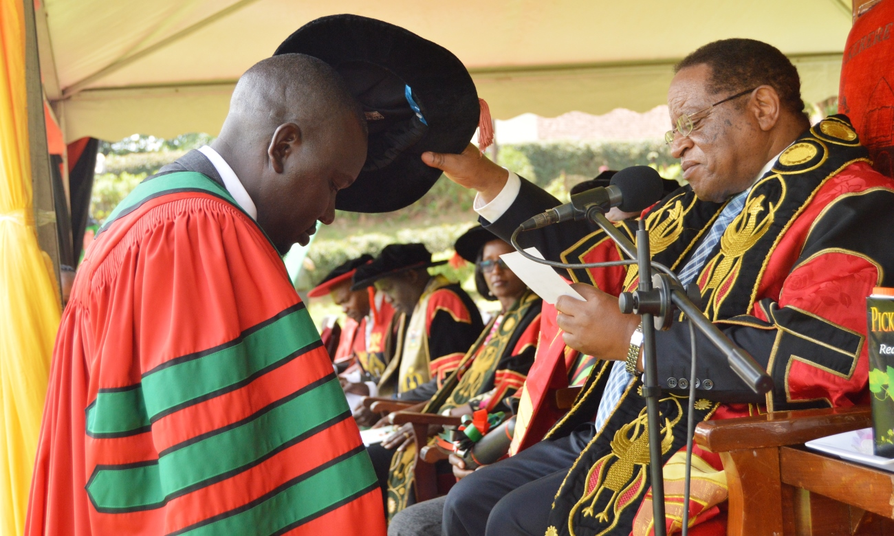 The Chancellor, Prof. Ezra Suruma confers a PhD upon a Male Graduand during Day 1 of the 69th Graduation Ceremony on 15th January 2019, Freedom Square, Makerere University, Kampala Uganda