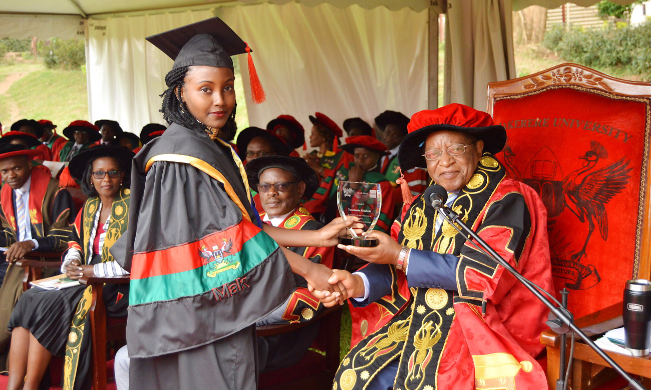 The Chancellor, Prof. Ezra Suruma (Right) hands over the ACCA Uganda Award to Ms. Tumukunde Elizabeth, the best performing student in Bachelor of Commerce (Accounting Option) during the 2nd Session of the 69th Graduation Ceremony on 16th January 2019 at Makerere University, Kampala Uganda.